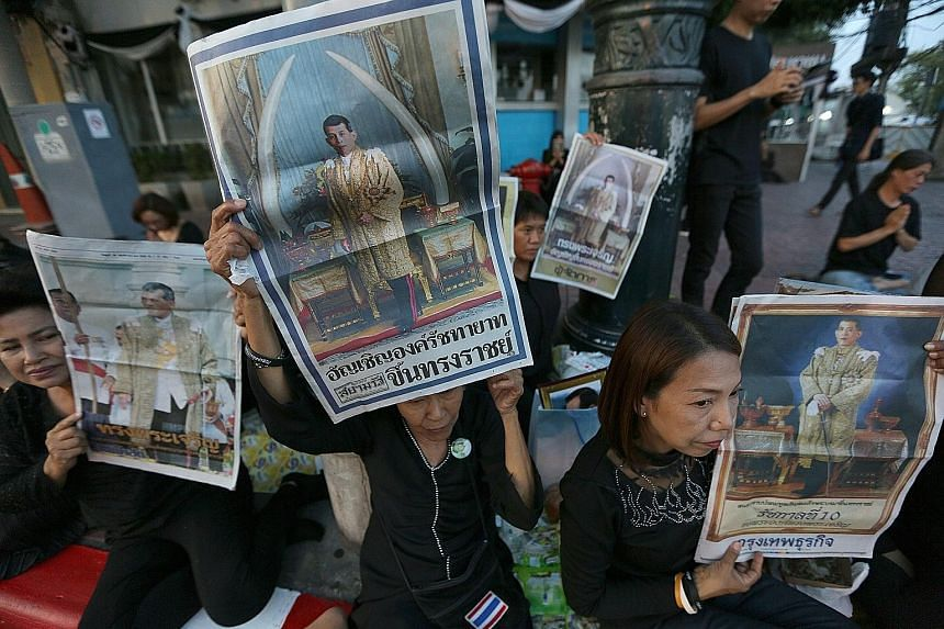Thai well-wishers holding up portraits of Thai Crown Prince Maha Vajiralongkorn on the front page of newspapers as they gathered outside the Grand Palace in Bangkok yesterday. The 64-year-old Crown Prince became Thailand's new king yesterday after in