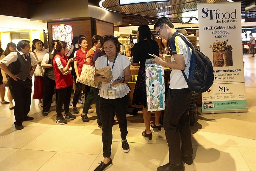 A snaking queue had formed around home-grown salted egg snack company The Golden Duck's semi-circular kiosk at Raffles City Shopping Centre yesterday morning. The morning downpour did not deter readers of The Straits Times from gathering at the mall'