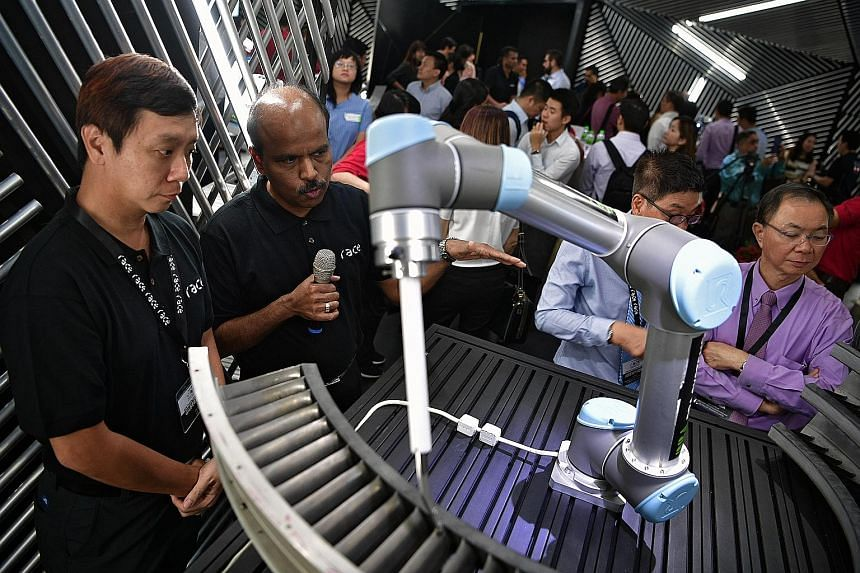 e2i CEO Gilbert Tan (left) taking a look at a compound remover with Race trainer A. S. Sundaram yesterday.