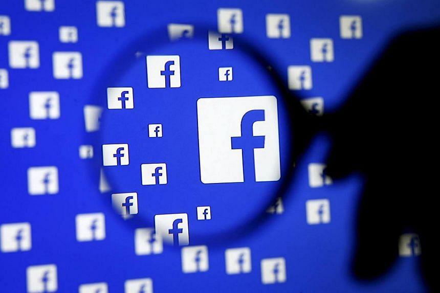 A man poses with a magnifier in front of a Facebook logo on display.