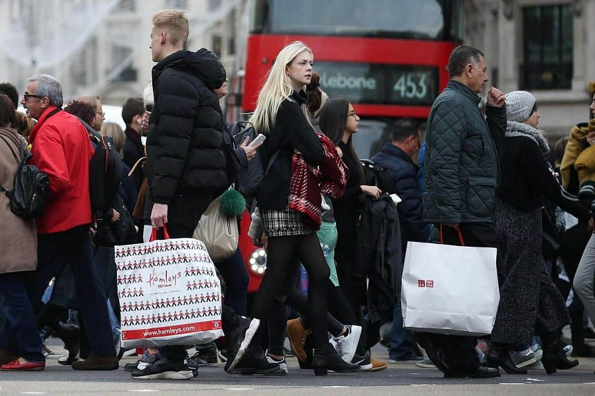 Pedestrians carrying shopping bags while crossing the street in Oxford Street in London on Oct 27, 2016.