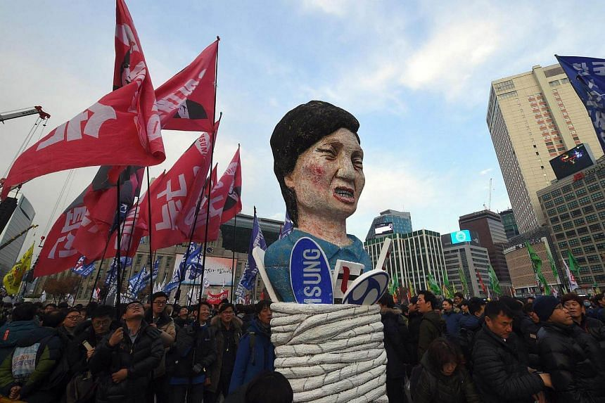 Protesters carry an effigy of South Korea's President Park Geun Hye during an anti-government rally demanding the resignation of the president in central Seoul, on Nov 30, 2016.