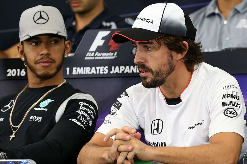 Fernando Alonso (right) speaks as Lewis Hamilton (left) looks on at a press conference ahead of the  Japanese Grand Prix in October 2016.