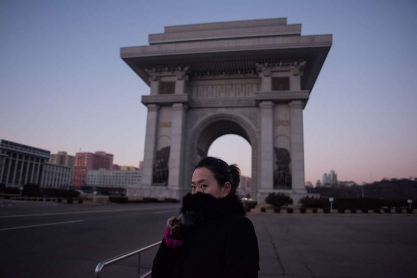 A tour guide shields her face from the cold as she stands before the Arch of Triumph in Pyongyang on Dec 1, 2016.