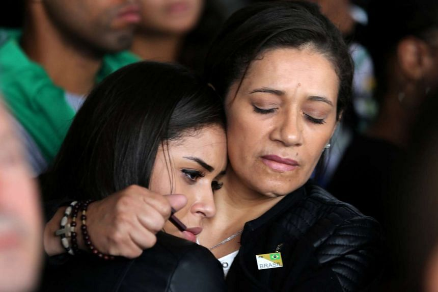 Relatives of the victims of the plane crash in Colombia react as the plane with the remains of the victims arrives.
