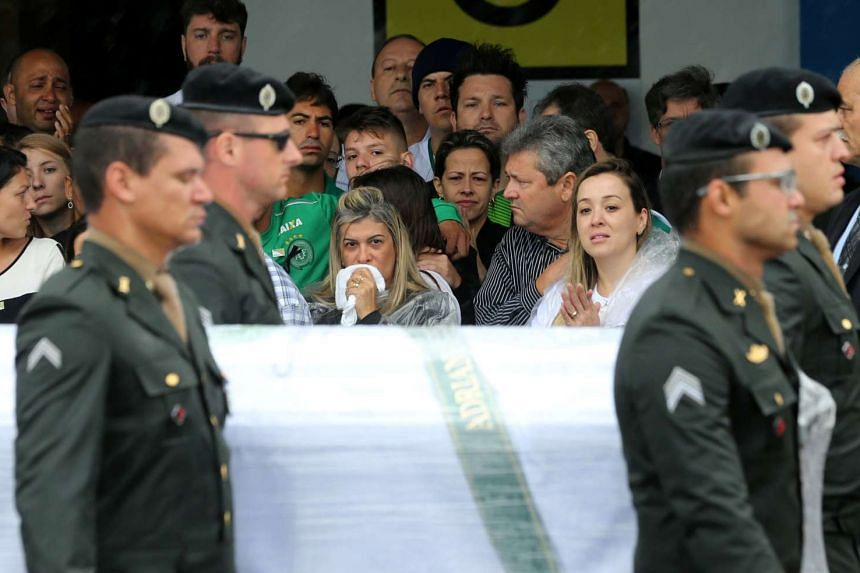Relatives look on as a coffin cointaining the mortal remains of a victim of the plane crash in Colombia arrives in Chapeco.