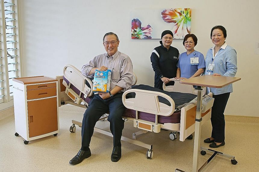 Mr Ee holding the Confidence diapers Home Care Enterprises is launching next month. He is seated on HCE's first product - an electric homecare bed. With him are (from far left) Ms Zahara, CGH senior nurse manager Fong Poh Chee and HCE coordinator Iri