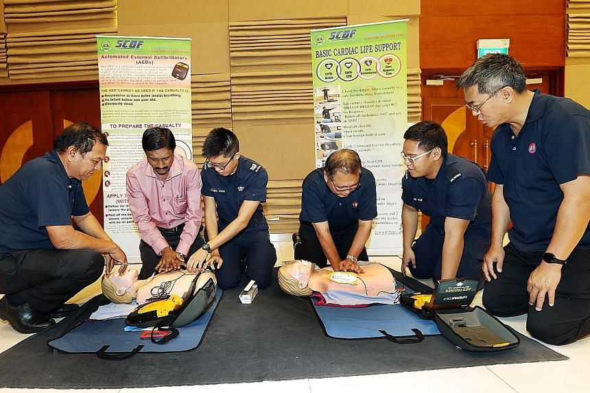 Singapore Civil Defence Force Third Sergeant Daniel Yuen (third from left) and Private Alif Irwan (fifth from left) instructing bus drivers how to perform cardiopulmonary resuscitation at yesterday's seminar.
