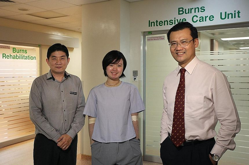 Ms Loy, with Dr Chew Khong Yik (left) and Associate Professor Tan Bien Keem, who were with her every day as she spent four months in hospital, enduring great pain during treatment. Prof Tan said the team was surprised by her positive attitude.