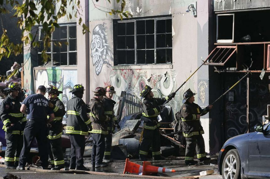 Firefighters working to clear debris from a doorway of a warehouse after a fire broke out that killed at least nine people, in Oakland, California on Dec 3, 2016.