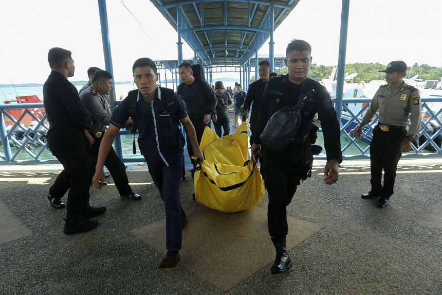 Police carry a body bag containing debris and belongings of passengers from a plane that went missing in Batam on Dec 4, 2016.