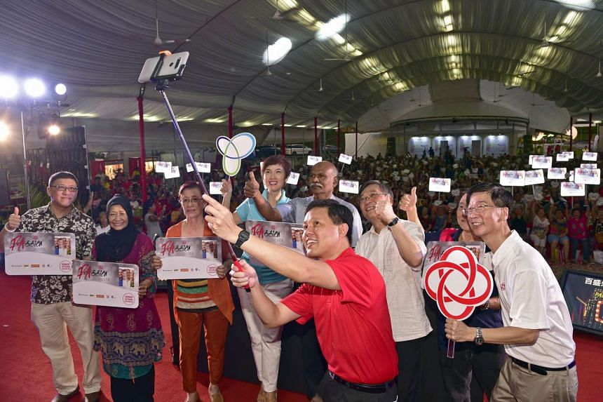 Mr Chan Chun Sing taking pictures with Health Minister Gan Kim Yong (third from right), Senior Minister of State Josephine Teo (centre, rear) and other guests and residents at the event, on Dec 4, 2016.