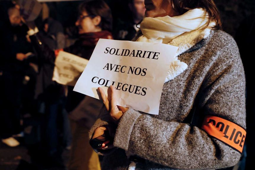 """Police officers gather during a demonstration in front of the police station in Evry on Oct 18, 2016. The banners read: """"Solidarity with our colleagues""""."""
