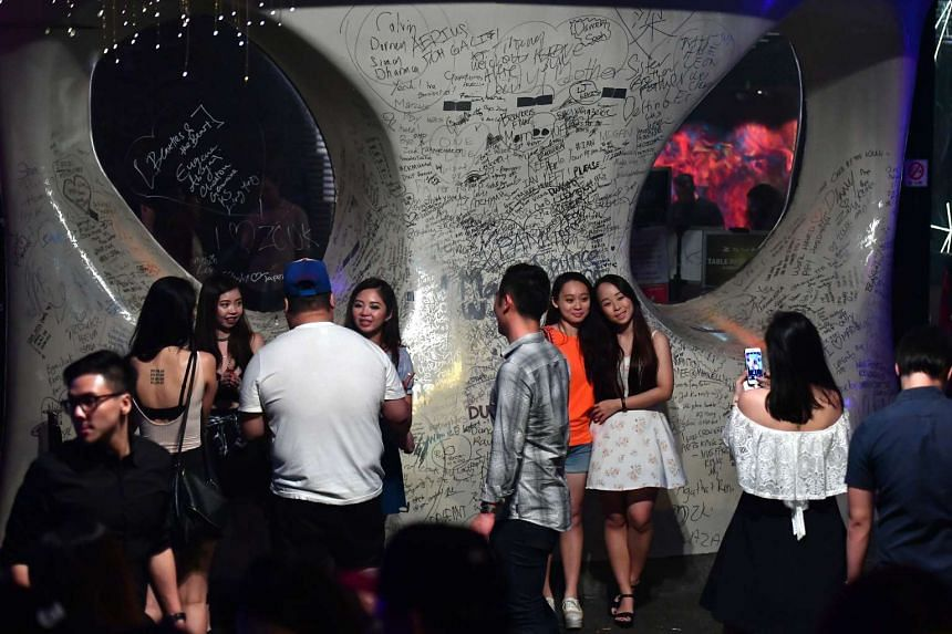 Partygoers take the chance to scribble goodbye notes and memories on the facade of Zouk with silver markers provided by the club.