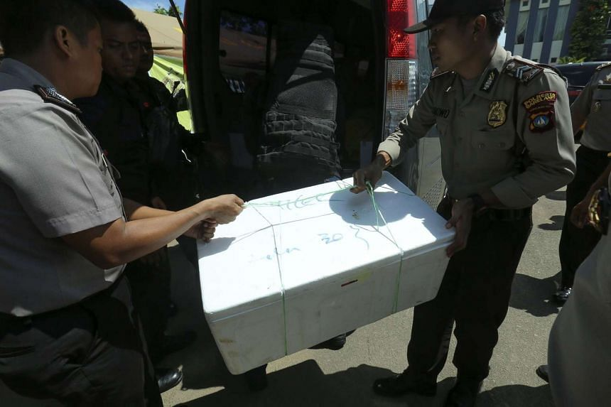 Police carry a box containing remains of victims from a plane that went missing in Batam on Dec 4, 2016.