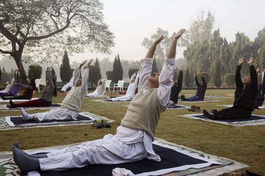People stretch while performing a yoga pose at Nehru Park in New Delhi, India, on Nov. 20, 2016.