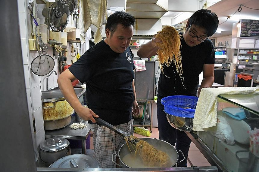 Mr Wong (left) and volunteer Lee Shi Hao, 26, preparing oyster mee suah for the elderly last month at 73@Hillcrest, a coffee shop by day and bistro by night.