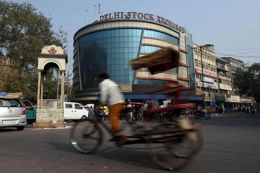 A cycle-rickshaw puller pedals past the Delhi Stock Exchange in New Delhi on Nov 30, 2016.