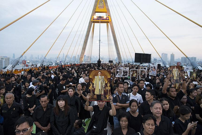 Thousands of Thais gathered on a Bangkok bridge named after the late King Bhumibol Adulyadej on what would have been his birthday yesterday, the latest organised mass display of grief in a nation adjusting to life without him. For much of his seven-d