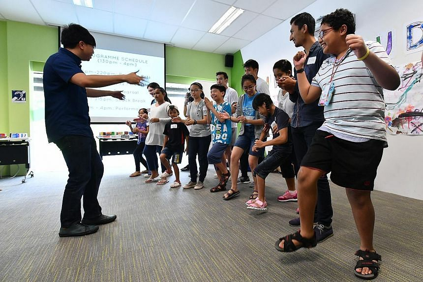 Conductor Wong Kah Chun leading the children in a body percussion session at The Enabling Village in Lengkok Bahru.
