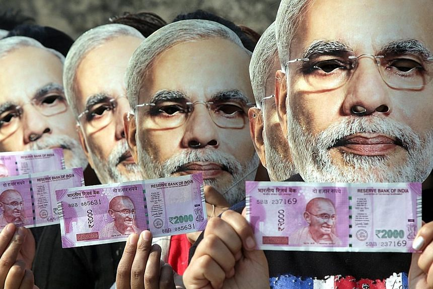 Demonstrators, wearing masks of Indian PM Narendra Modi, holding new currency notes in support of his move to ban 500- and 1,000-rupee notes, in Jammu, Kashmir, last month. The rise of underground networks illustrates the challenge he faces in trying