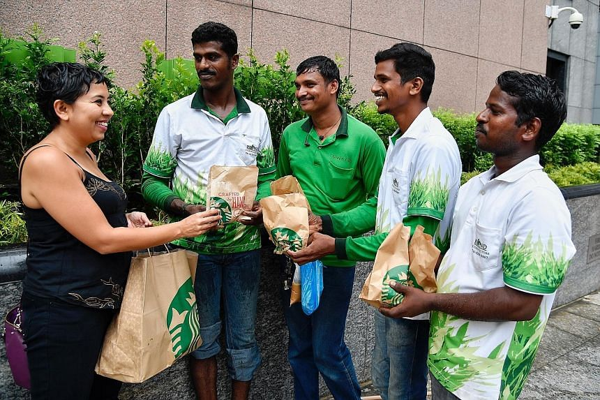 Ms Dipa Swaminathan distributing some of the food items from Starbucks outlets to foreign workers (from left) Satish Kumar, 30; Sundara Murthy, 26; Vijay Kumar, 30; and Ganeshan Siva Kumar, 29.