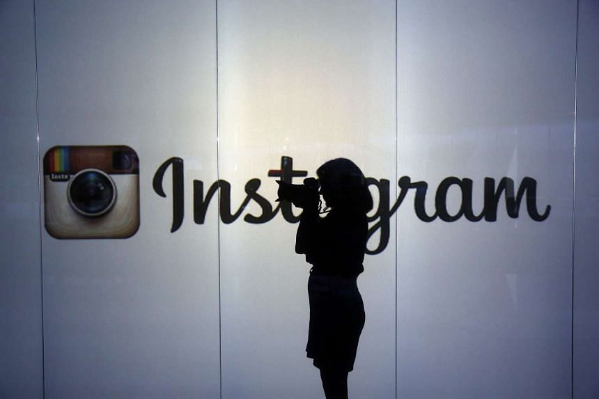 A woman takes a photograph with a digital slr camera whilst standing against an illuminated wall bearing Instagram Inc.s logo in this arranged photograph in London, UK, on Jan. 5, 2016.