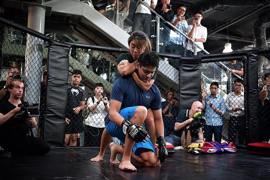 Angela Lee, One Championship's first female world champion, shows Singapore's Olympic swimming gold medallist Joseph Schooling how to execute a choke hold at Evolve MMA gym at Far East Square.