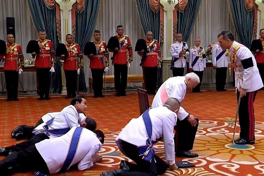 A screen grab from Thai TV on Dec 1 showed privy council president Prem Tinsulanonda (with pink sash) bowing and Prime Minister Prayut Chan-o-cha prostrating as he looked up to King Maha Vajiralongkorn.