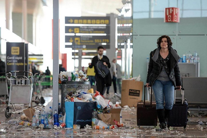 A passenger pulling two pieces of luggage in a hall of Barcelona-El prat aiport, littered with pieces of paper and rubbish during a strike of the airport cleaning staff in El Prat de Llobregat on Dec 2, 2016.