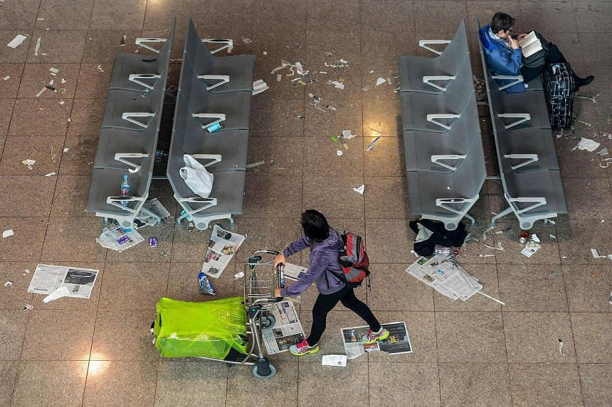 A passenger pushing a trolley in a hall of Barcelona-El prat aiport, littered with pieces of paper and rubbish during a strike of the airport cleaning staff in El Prat de Llobregat on Dec 2, 2016.