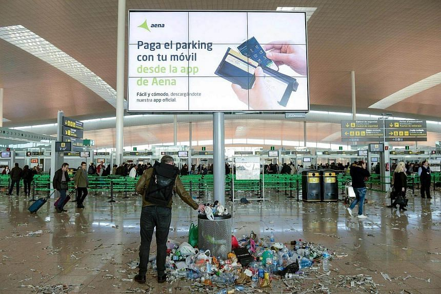 A passenger puts an object in a rubbish bin surrounded by pieces of paper and rubbish in a hall of Barcelona-El prat aiport, during a strike of the airport cleaning staff in El Prat de Llobregat on Dec 2, 2016.