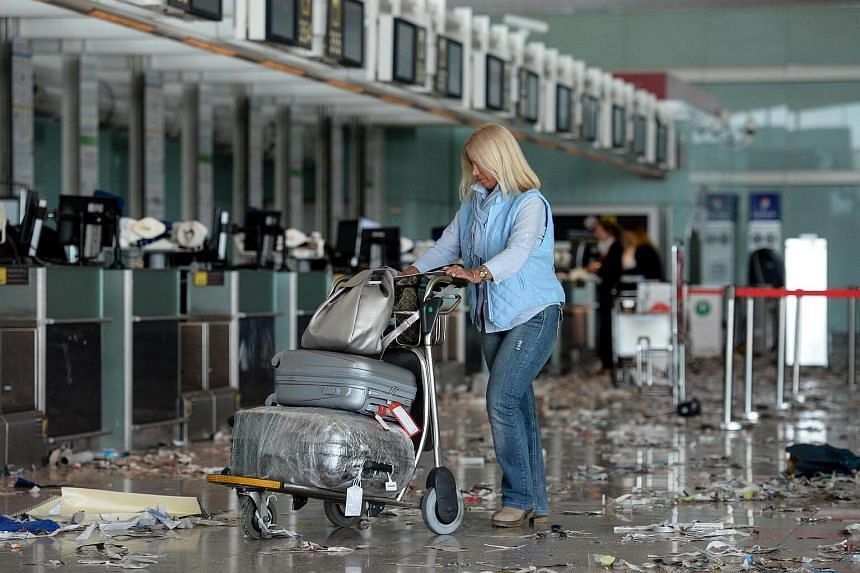 A passenger pushing a trolley in a hall of Barcelona-El prat aiport, littered with pieces of paper and rubbish during a strike of the airport cleaning staff in El Prat de Llobregaton Dec 2, 2016.