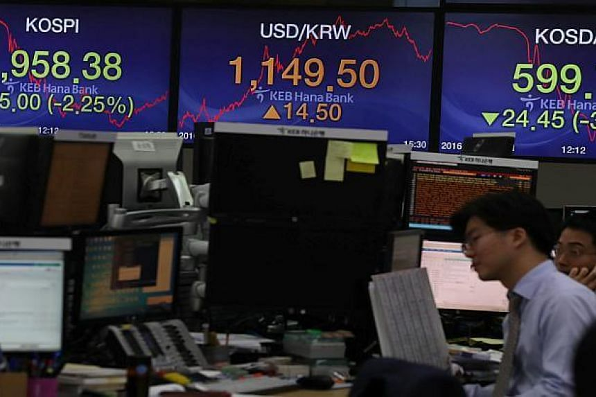 Currency dealers work in front of electronic boards showing the Korea Composite Stock Price Index (KOSPI) and the exchange rate between the US dollar and South Korean won, at a dealing room of a bank in Seoul, South Korea on Nov 9, 2016.