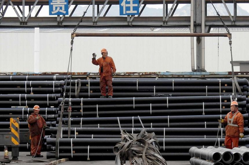Chinese workers loading steel tubes onto a truck at a logistics center in Lianyungang in China's Jiangsu province.