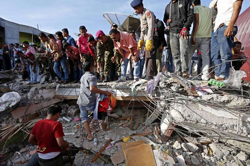 Members of an Indonesian rescue team and local residents searching for victims using an excavator after an earthquake struck Pidie Jaya district, Aceh, Indonesia on Dec 8, 2016.