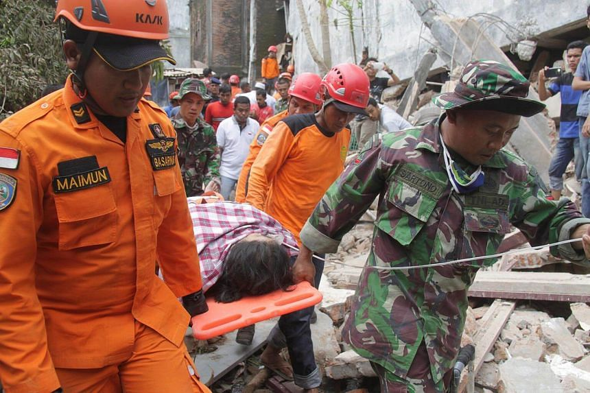 Indonesian rescue workers carry a survivor from a fallen building after an earthquake in Ulee Glee, in the northern province of Aceh, Indonesia.