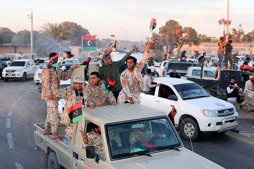 Libyan fighters celebrating after taking ISIS' coastal stronghold.