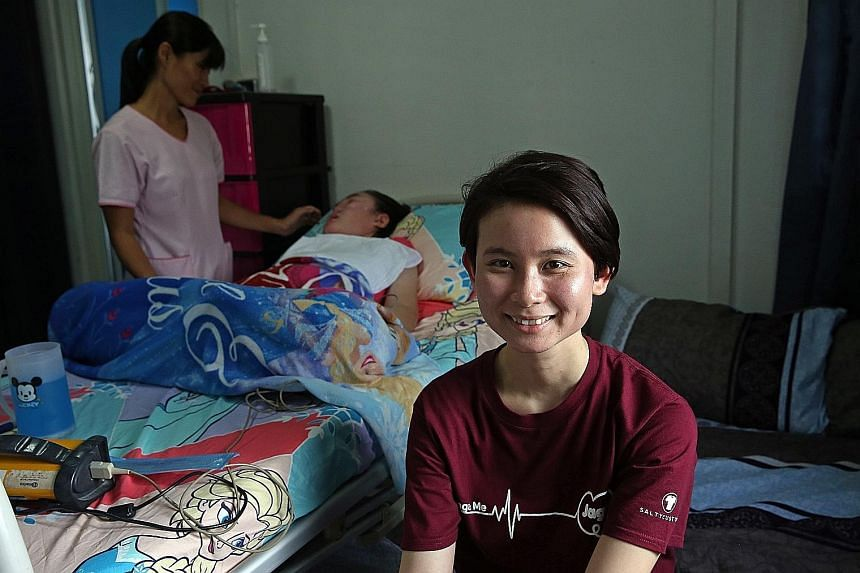Jaga-Me co-founder Kuah Ling Ling (foreground), 30, in the home of patient Bella Tan, who is being attended to by HCA Hospice Care nurse Serene Wong, 41. Jaga-Me helped HCA provide a nurse on short notice to relieve Bella's mother when she could not