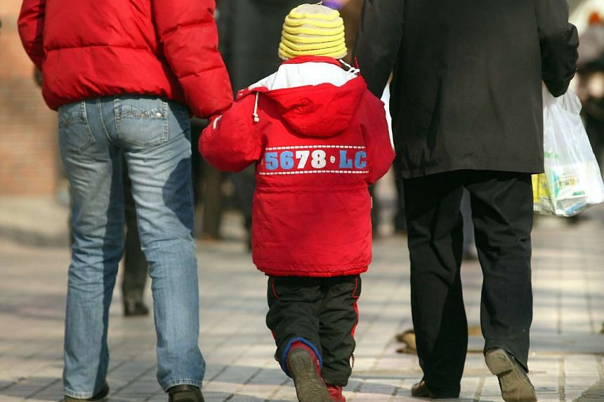 Chinese parents walk their son to a children's hospital in Beijing, China on Jan 23, 2007.