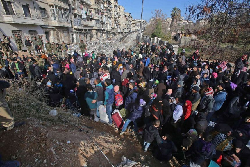 Syrian residents fleeing the violence gather at a checkpoint in the Maysaloun neighbourhood of Aleppo on Dec 8, 2016.
