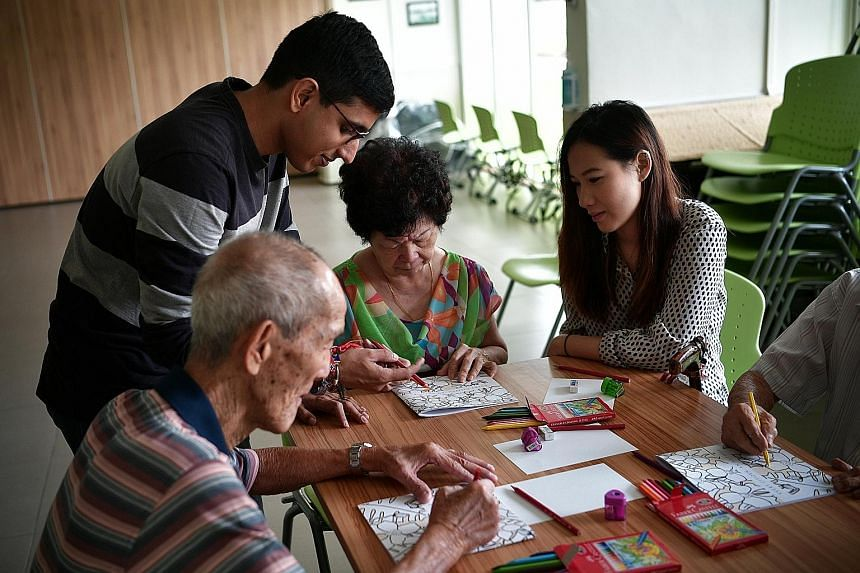 Mr Upadhiah and Ms Tan with Madam Lam and other participants of the inter-generational book project at St Luke's ElderCare Clementi Centre last week.