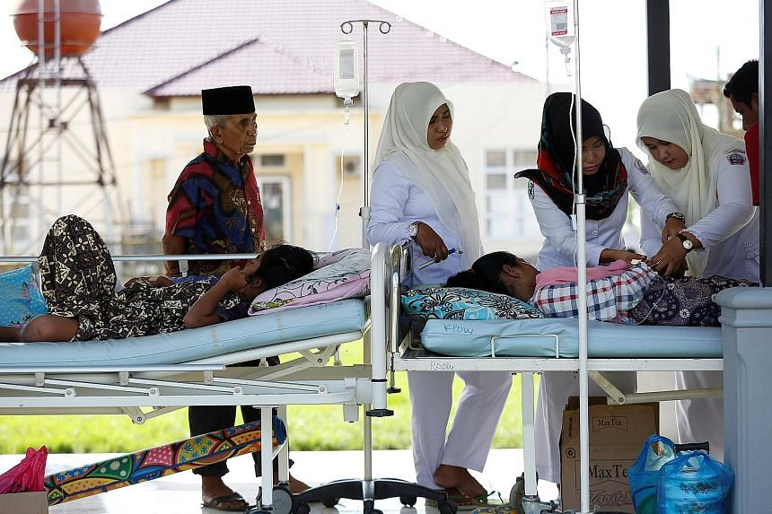Earthquake victims being attended to outside a hospital in Meureudu, Pidie Jaya, in Aceh province yesterday. The Indonesian Embassy in Singapore says it has received many queries from people who want to help.