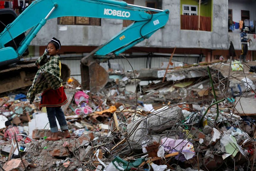 A boy standing on rubble from a collapsed building following this week's strong earthquake in Meureudu market, Pidie Jaya, Aceh province, Indonesia, on Dec 9, 2016.