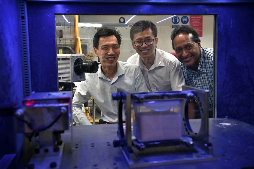 NUS professors (from left) Vincent Tan, Darren Chian and Anand Sarma with a machine used to test the ability of sand to absorb energy exerted on it. Steel would melt on impact if hit by armour-piercing ammunition shot from a high-velocity rifle. In c