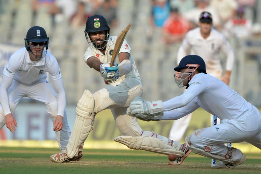 India's Cheteshwar Pujara (centre) playing a shot on the second day of the fourth Test cricket match between India and England at the Wankhede stadium in Mumbai, on Dec 9, 2016.