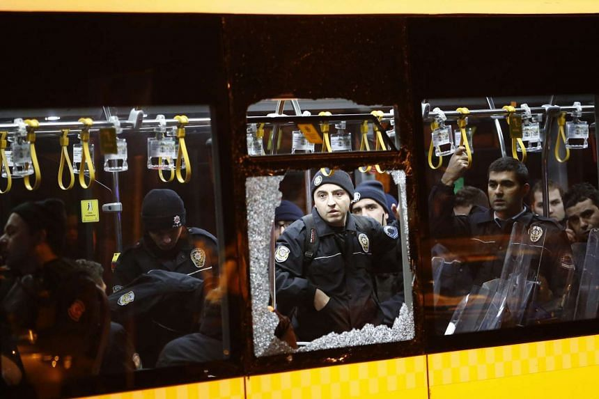 Police officers stand inside a damaged bus after an explosion at the Vodafone Arena in Istanbul, Dec 10, 2016.