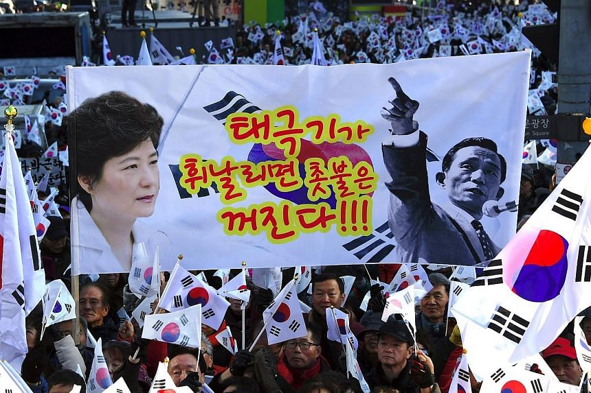 "A pro-Park banner with portraits of Ms Park and her father Park Chung Hee (above) and a placard (below) saying ""Park Geun Hye Out""."