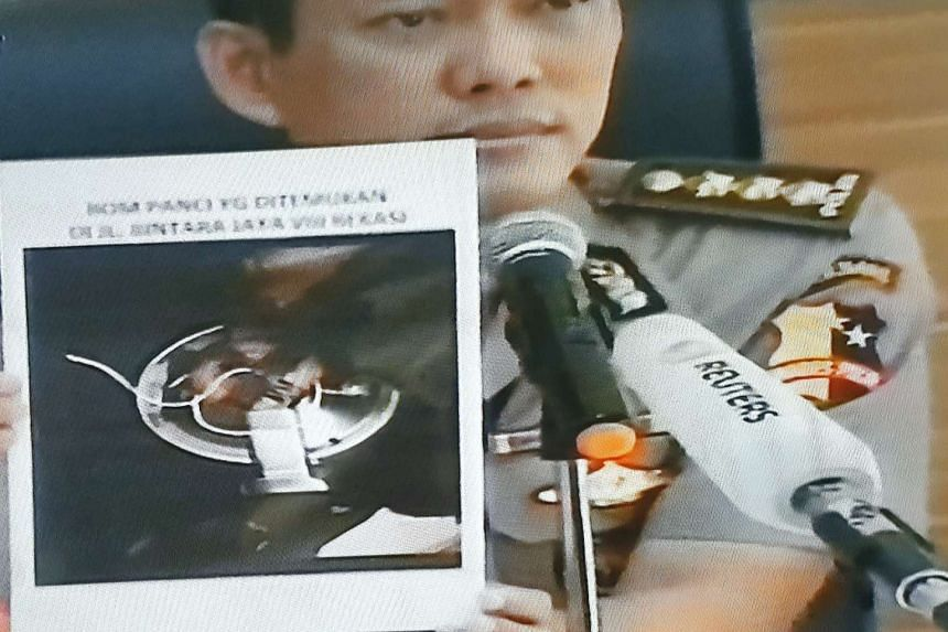 """Jakarta police spokesman Awi Setiyono showing a photograph of the """"rice cooker bomb""""."""
