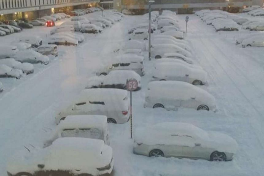 Cars outside Sapporo's New Chitose Airport lie covered in snow, on Dec 12, 2016.
